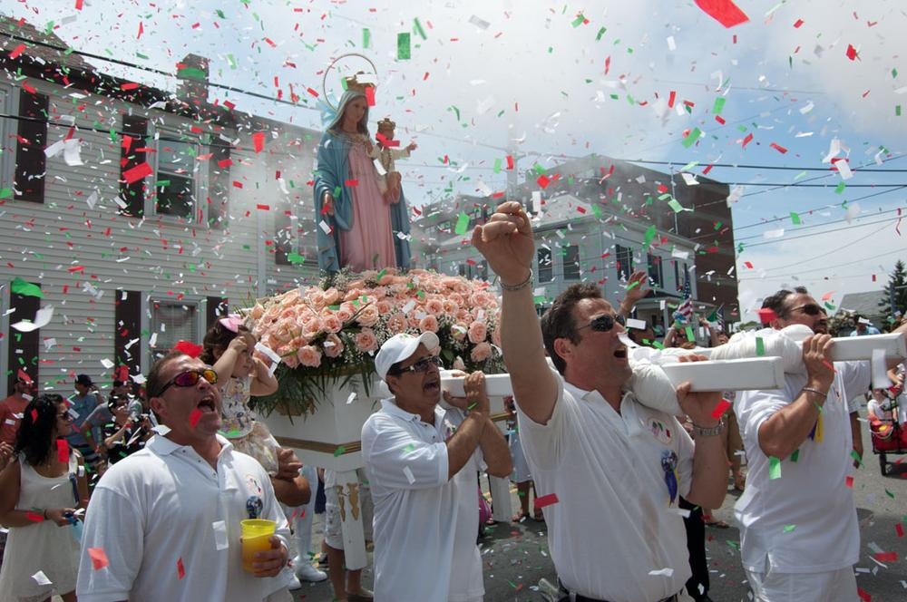 Men carrying the Mother of Grace statue shout blessings on Prospect Street during Sunday's procession. (Greg Cook)
