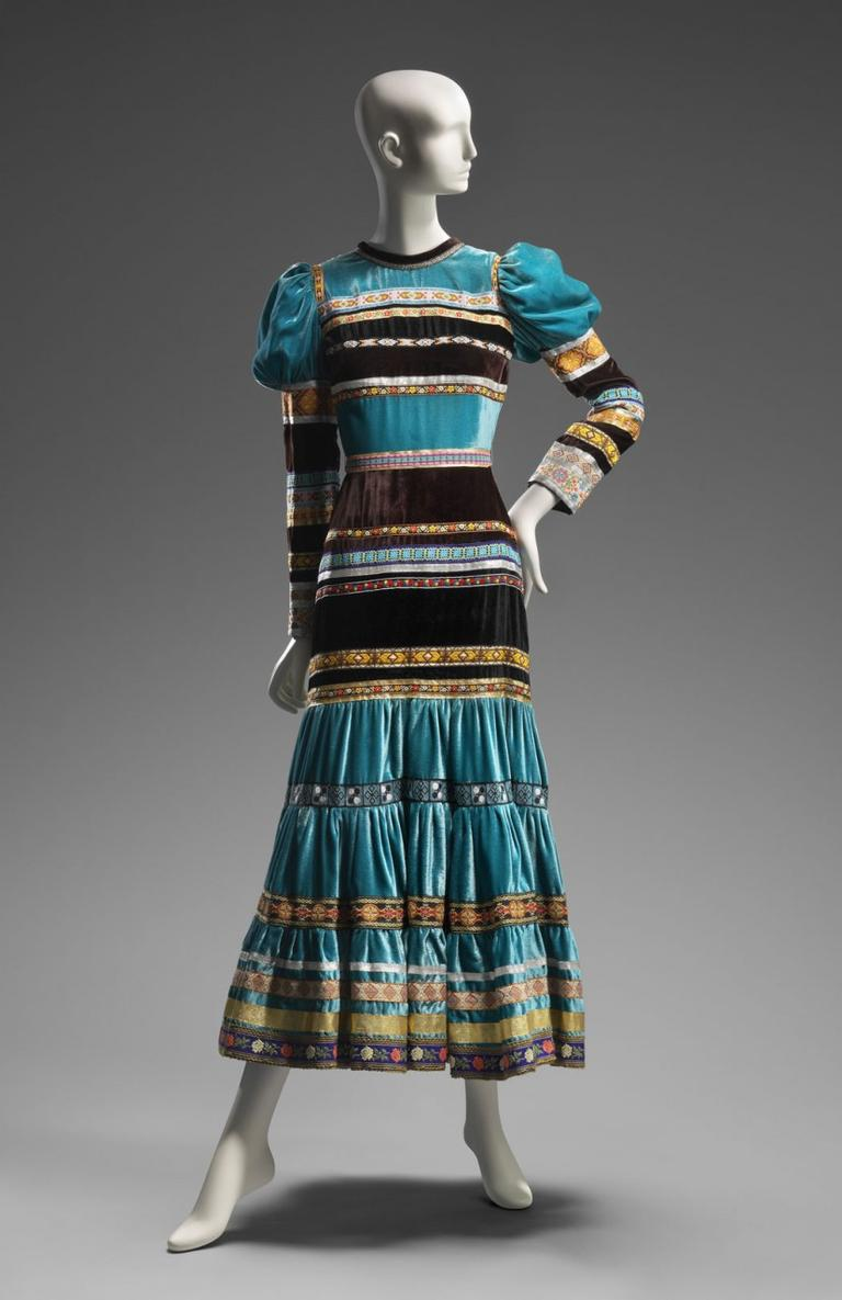 "Giorgio di Sant'Angelo's 1970 sapphire blue rayon velvet dress incorporated the puffed sleeves and long skirt of the ""prairie hippie"" look with horizontal ribbons that evoke 19th century Native American dresses. (Courtesy of the Museum of Fine Arts, Boston)"