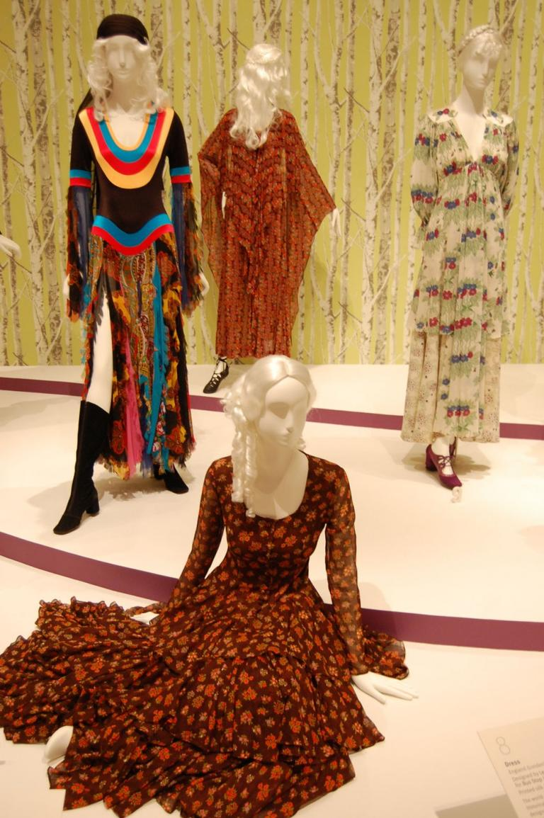 "Betsey Johnson's 1969 printed cotton dress (foreground) imitated ""Gone with the Wind"" fashions but enlarges the usual calico flower print to give it a '60s kick. Designers also took inspiration from gypsies (left) and the knights and ladies of the 1967 film ""Camelot"" (center background). (Greg Cook)"
