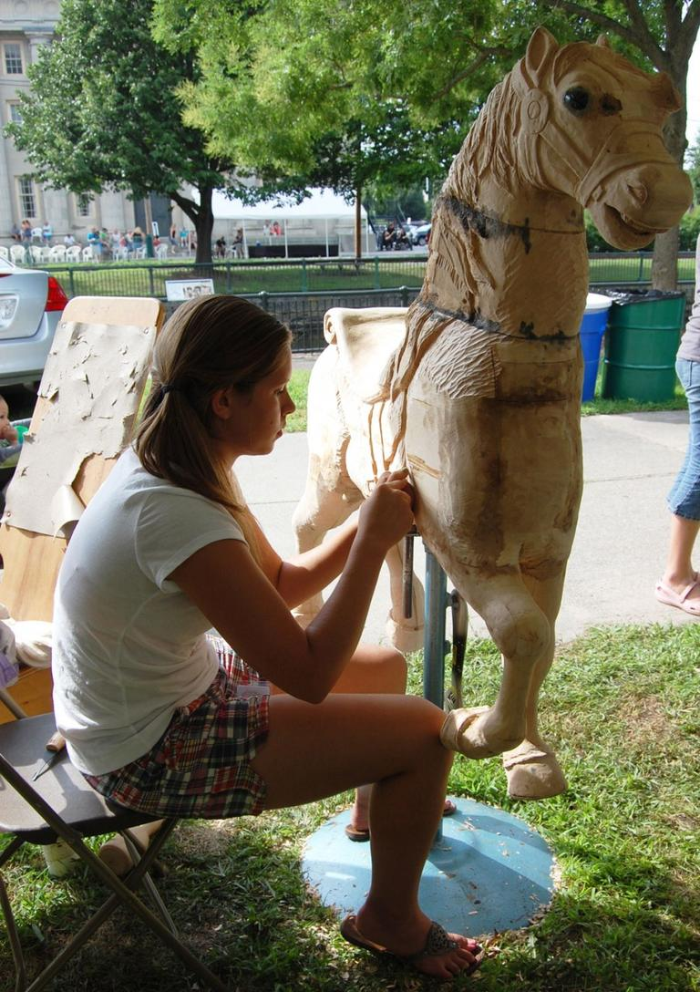 """I saw [a carousel horse] at the state Augusta show and it won best in show. Thirteen-year-old me decided to have big ambitions and do it,"" says Ellyzabeth Bencivenga of Limestone, Maine, who has been carving her full-sized carousel horse for three years now. She says the project has taught her ""patience."" (Greg Cook)"