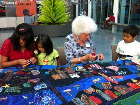 "Clara Wainwright (center) guides work on the ""Mending Boston"" quilt at the Museum of Fine Arts. (Courtesy photo)"