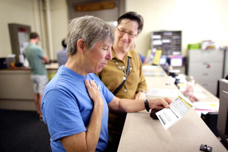 Lisa Kesser, front, reacts while completing paperwork to obtain a marriage license with her partner of 20 years, Dorcey Baker, at Providence City Hall Thursday. (Steven Senne/AP)