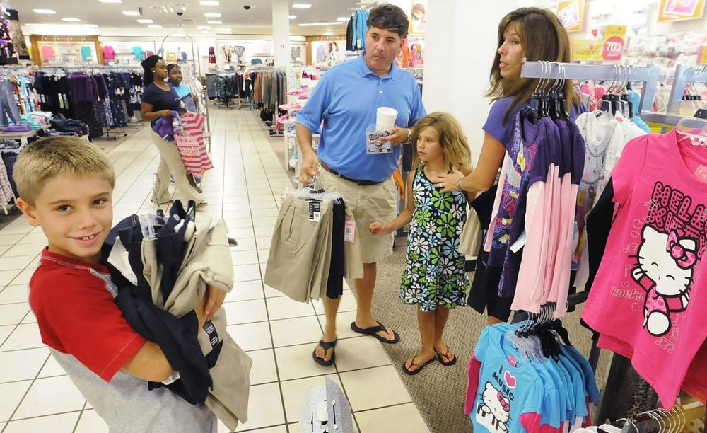 Andy and Aimee Smith, background, and their children Ian, left, and Riley shop for back-to-school clothes during the first day of the sales tax holiday at J.C. Penney in Eastdale Mall in Montgomery, Ala. in August 2011. (Mickey Welsh/Montgomery Advertiser via AP)