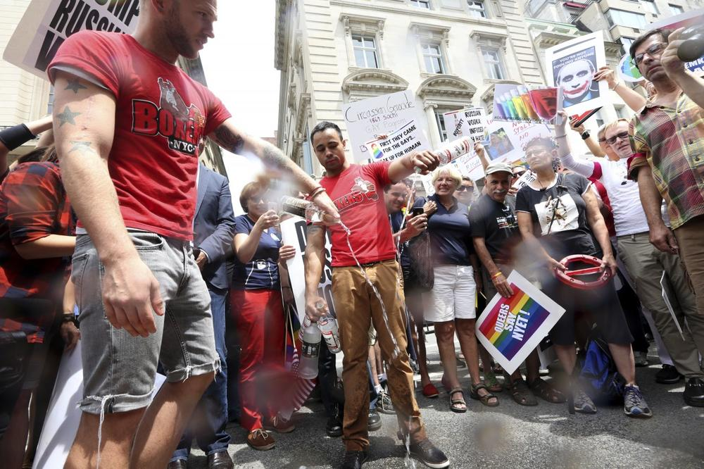 Gay rights supporters pour out Russian vodka in New York in front of the Russian Embassy on July 31 as they protest warnings to gay Olympic athletes coming to Sochi for the 2014 Winter Games. (AP)