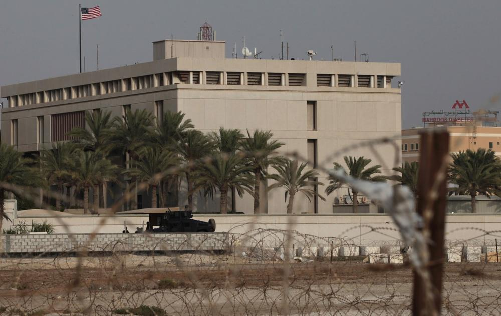 A Bahraini armored personnel vehicle and personnel reinforce U.S. Embassy security just outside of a gate to the building, surrounded in barbed wire, in Manama, Bahrain, on Sunday, Aug. 4, 2013. (Hasan Jamali/AP)