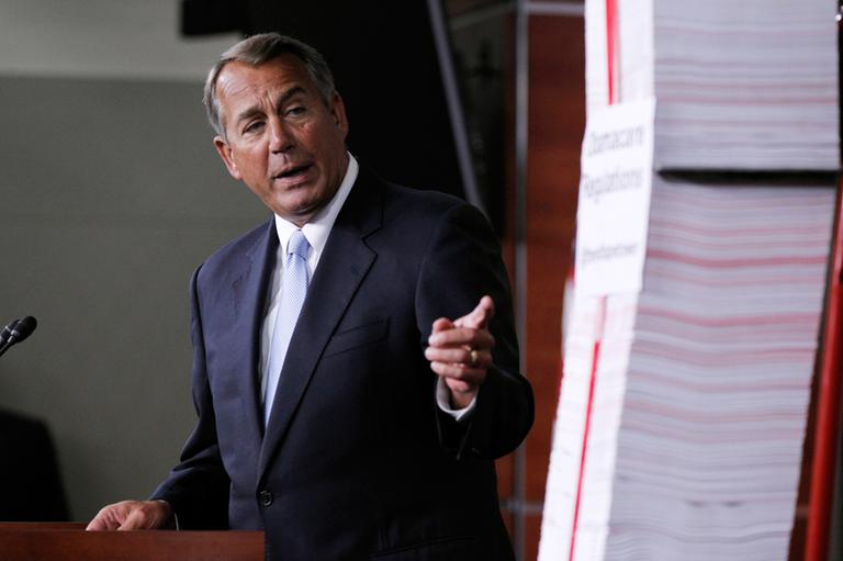 In this May 16, 2013 file photo, House Speaker, Republican John Boehner of Ohio, points toward the tall stack of paper, representing 20,000 pages of Affordable Care Act regulations, during a news conference on Capitol Hill in Washington. (Molly Riley/AP File)
