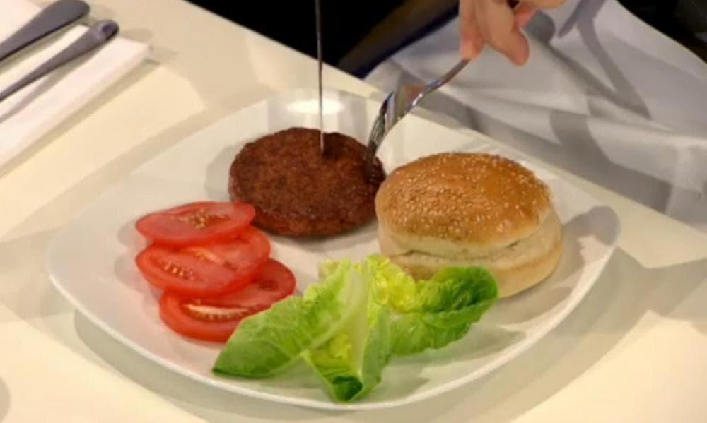 The world's first lab-grown hamburger is eaten in London. (BBC video screenshot)