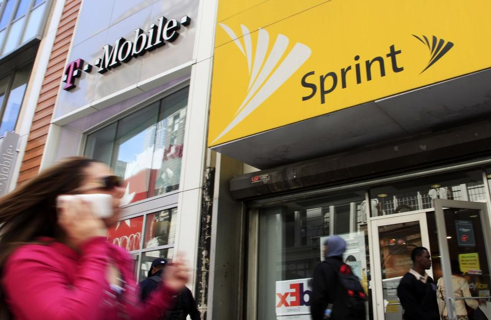 A woman using a cell phone walks past T-Mobile and Sprint stores in New York. Sprint and T-Mobile are eating into AT&T and Verizon's consumer bases. (Mark Lennihan/AP)