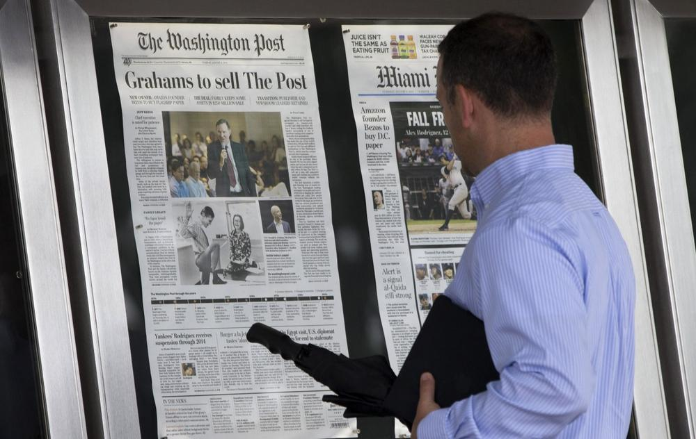 A visitor views the front page of the Washington Post, displayed outside the Newseum in Washington, Tuesday, Aug. 6, 2013, a day after it was announced that Amazon.com founder Jeff Bezos bought the Washington Post for $250 million. (Evan Vucci/AP)