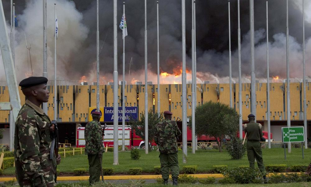 Police stand guard as fire engulfs the International arrivals unit of Jomo Kenyatta International Airport, Nairobi, Kenya, Wednesday Aug. 7, 2013. (Sayyid Azim/AP)
