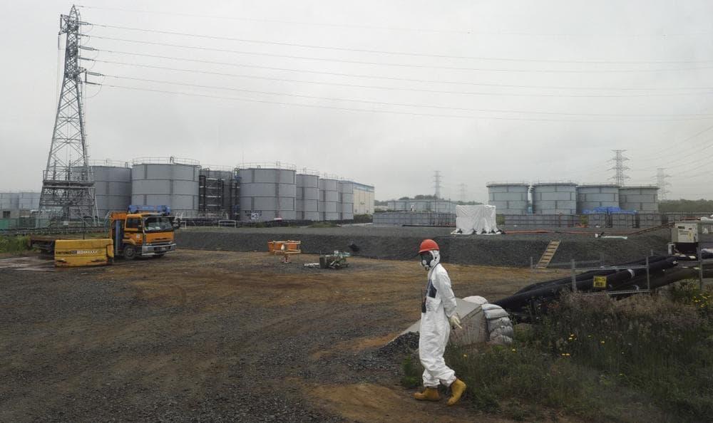 A construction worker walks beside the underground water tank and water tanks at the Fukushima Dai-ichi nuclear plant at Okuma in Fukushima prefecture, Japan, June 12, 2013. (Toshifumi Kitamura/AP)