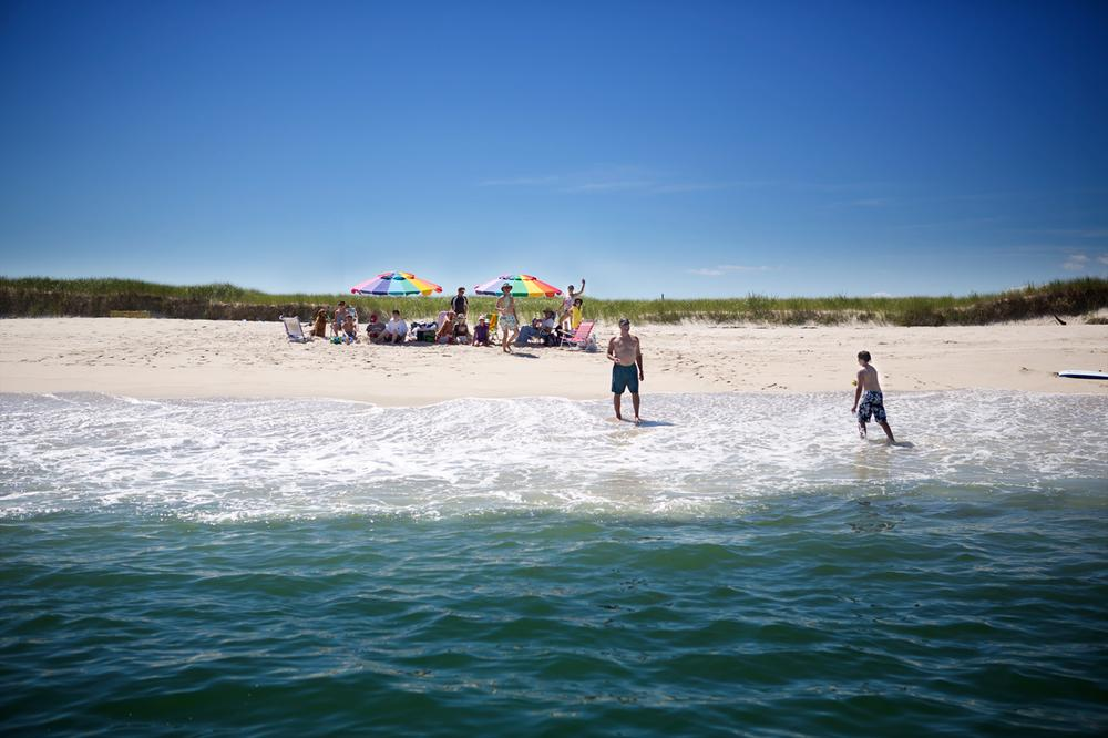 A group of beachgoers listened to a warning from the OCEARCH crew about sharks in the vicinity. (Jesse Costa/WBUR)