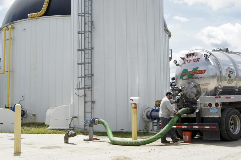 A truck driver offloads waste from Home Market Foods in Norwod into the anaerobic digester. (Lynn Jolicoeur/WBUR)