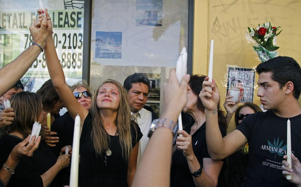 Offir Hernandez, third from left, the sister of Israel Hernandez-Llach, leads a group of mourners in holding candles to the sky in memory of her brother. Family members, friends, schoolmates and fans gathered at in Miami Beach for a vigil on Thursday, Aug. 8, 2013. (Carl Juste/Miami Herald)