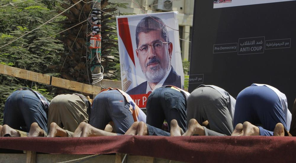 Supporters of Egypt's ousted President Mohammed Morsi pray in front of his poster in Nahda Square, where protesters have installed their camp near Cairo University in Giza, southwestern Cairo, Egypt, Monday, Aug. 12, 2013. (Amr Nabil/AP)