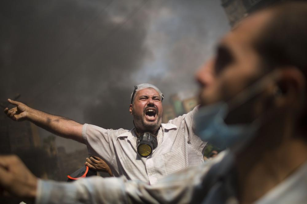 Supporters of ousted Islamist President Mohammed Morsi shout during clashes with Egyptian police at the Rabaah Al-Adawiya protest camp in Cairo's Nasr City district, Egypt, Wednesday, Aug. 14, 2013. (Manu Brabo/AP)