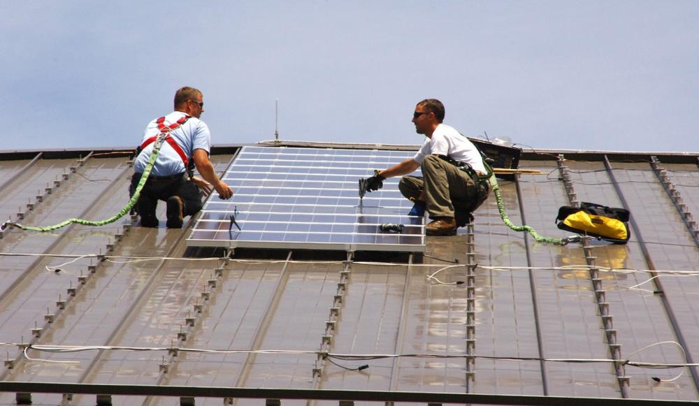 Two workers install solar panels on a rooftop in Fort Dix, Texas. (U.S. Army Environmental Command/Flickr)