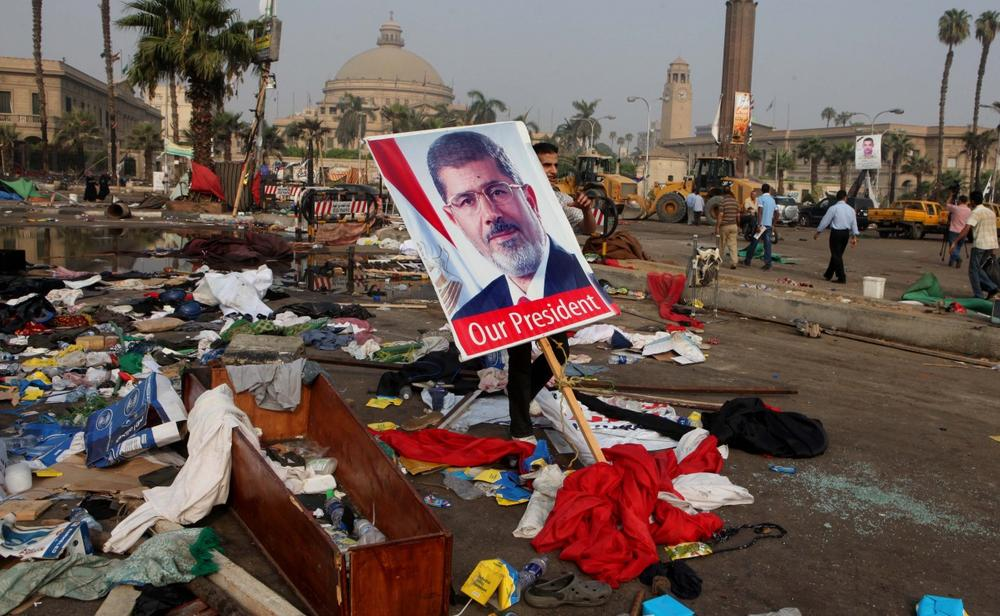An Egyptian carries a poster of Egypt's ousted President Mohammed Morsi among debris from a protest camp in Nahda Square, Giza, Cairo, Egypt, Thursday, Aug. 15, 2013. (Amr Nabil/AP)