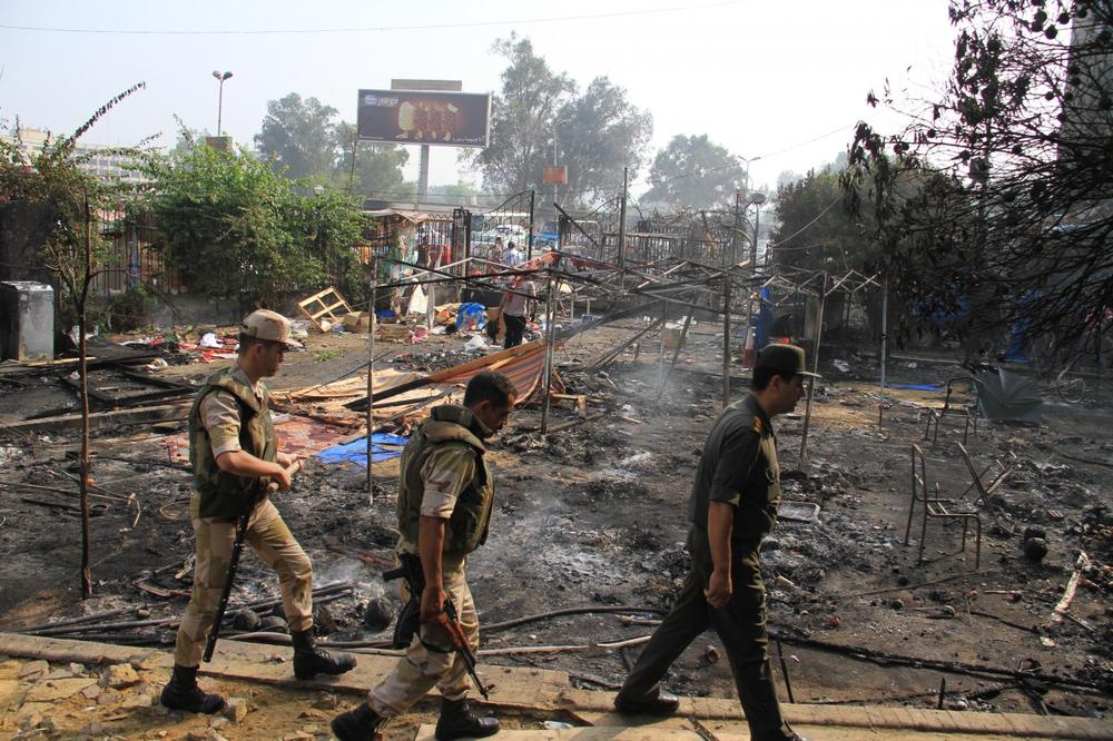 Members of the Egyptians Army walk among the smoldering remains of the largest protest camp of supporters of ousted President Mohammed Morsi, that was cleared by security forces, in the district of Nasr city, Cairo, Egypt. (Ahmed Gomaa/AP)