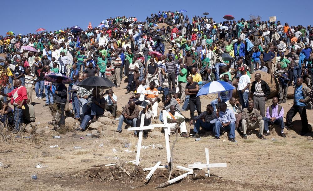 Mine workers sit on a hill where a year ago, police opened fire on fellow workers killing 34 and injuring 78, during a memorial service near the Marikana, South Africa, platinum mine, Friday Aug. 16, 2013. (Themba Hadebe/AP)