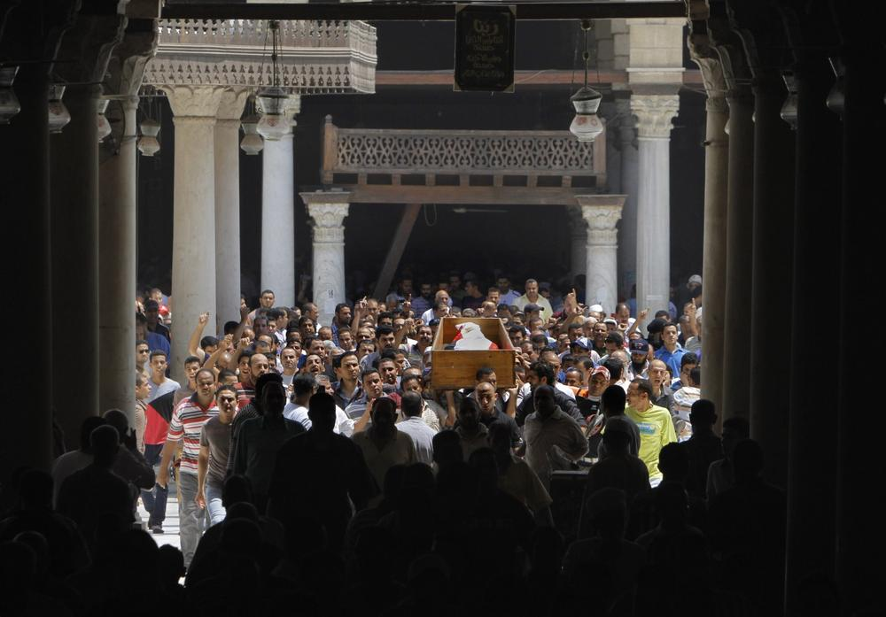Supporters of Egypt's ousted President Mohammed Morsi surround the coffin of their colleague who was killed during Wednesday' clashes, in Amr Ibn Al-As mosque before funeral prayers, in Cairo, Egypt, Friday, Aug. 16, 2013. (Amr Nabil/AP)