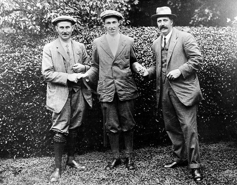 In this 1913 file photo, American golfer Francis B. Ouimet, center, shakes hands with Harry Vardon, left, and Ted Ray at the U.S. Amateur championship at The Country Club in Brookline, Mass. Ouimet's victory 100 years ago helped turn him and caddie Eddie Lowery into household names and boosted the sport's popularity. (AP)