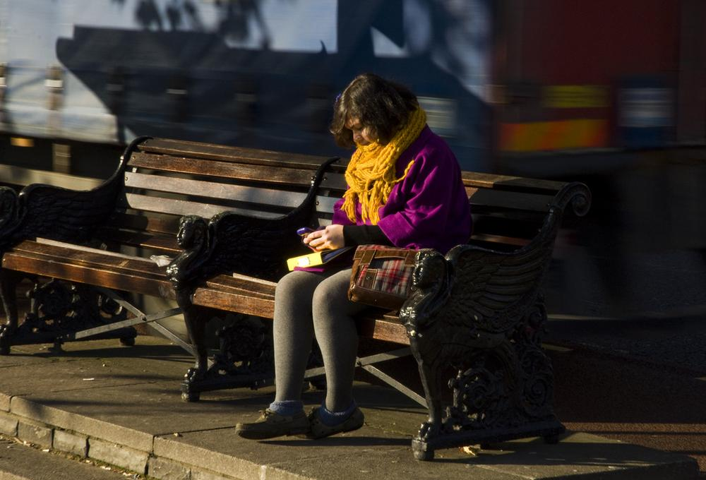 A girl texts on a bench. (James Offer/Flickr)