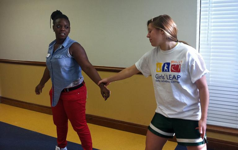 Monique Blocker, a violence intervention/prevention youth leader for the Madison Park Development Corporation in Roxbury, learns a wrist breakaway from a Girls' LEAP volunteer. (Delores Handy/WBUR)