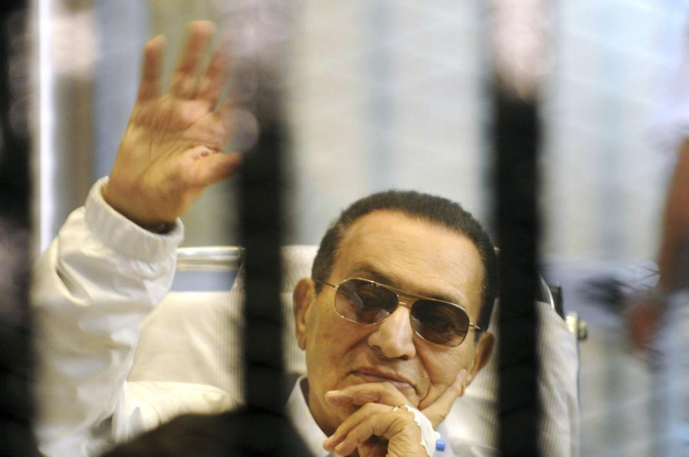 In this April 13, 2013, photo, former Egyptian President Hosni Mubarak waves to his supporters from behind bars as he attends a hearing in his retrial on appeal in Cairo, Egypt. (AP)