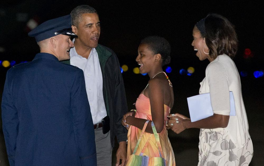President Barack Obama, second from left, Sasha Obama, and first lady Michelle Obama, are greeted as they exit Air Force One on arrival at Andrews Air Force Base, Md., on Sunday Aug. 18, 2013, after a family vacation on the island of Martha's Vineyard. (Jacquelyn Martin/AP)