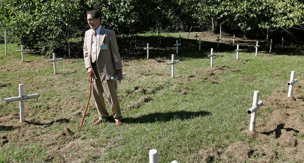 Dick Colon, a member of the White House Boys, walks through grave sites near the Arthur G. Dozier School for Boys in Marianna, Fla., Oct. 21, 2008. (Phil Coale/AP)