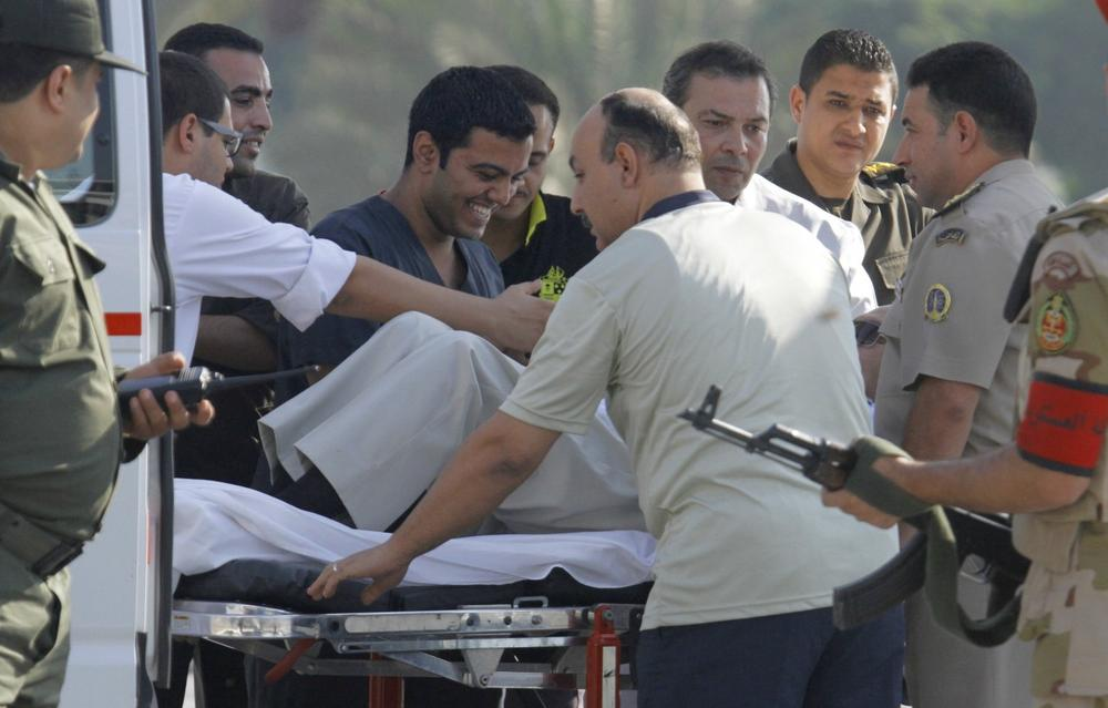 Egyptian medics share a laugh with former Egyptian President Hosni Mubarak, 85, as they escort him into an ambulance in, Cairo, Egypt, Thursday, Aug. 22, 2013. Mubarak has been released from jail and taken to military hospital in Cairo. (Amr Nabil/AP)