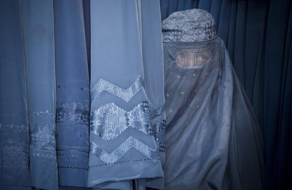 An Afghan woman peers through the the eye slit of her burqa as she waits to try on a new burqa in shop in the old town of Kabul, Afghanistan, April 11, 2013. (Anja Niedringhaus/AP)