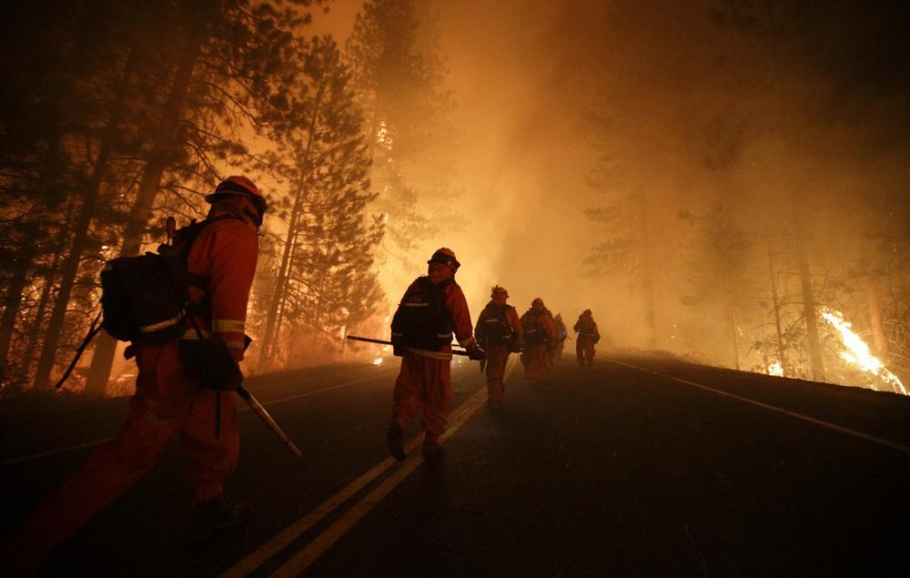 Inmate firefighters walk along Highway 120 as firefighters continue to battle the Rim Fire near Yosemite National Park, Calif., on Sunday, Aug. 25, 2013. (Jae C. Hong/AP)
