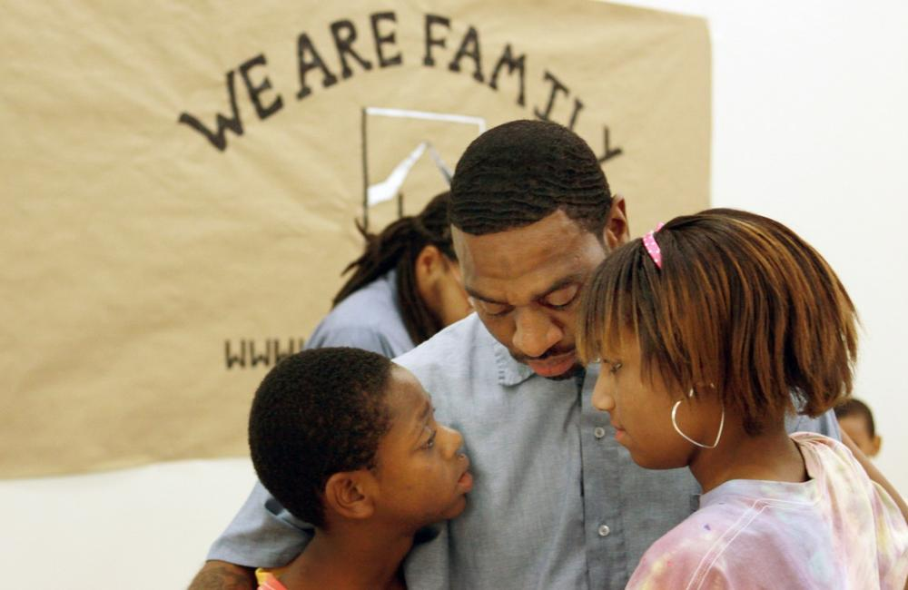 Geray Williams, an inmate at the North Branch Correctional Institution in Cumberland, Md., says goodbye to his children, Sanchez, 12, and Summer Williams, 13, during the closing minutes of a weeklong summer day camp at the maximum security prison, July 30, 2010. (Timothy Jacobsen/AP)