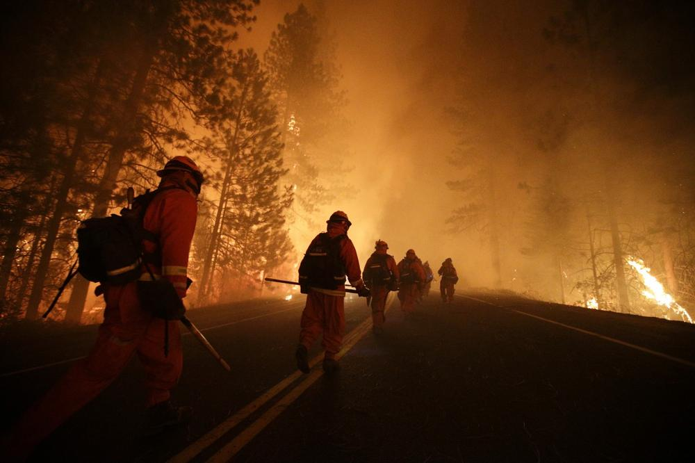 Inmate firefighters walk along Highway 120 as firefighters continue to battle the Rim Fire near Yosemite National Park, Calif., on Sunday, Aug. 25, 2013. Fire crews are clearing brush and setting sprinklers to protect two groves of giant sequoias as a massive week-old wildfire rages along the remote northwest edge of Yosemite National Park. (Jae C. Hong/AP)