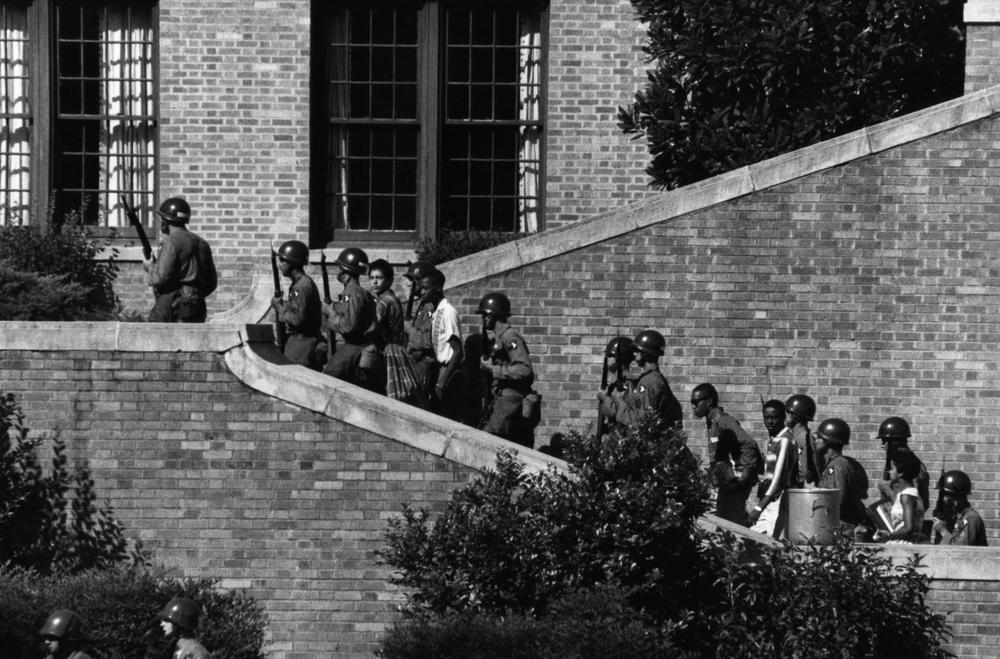 Members of the Little Rock Nine are escorted into Central High School, in 1957. They were the first black children to attend the all-white school. (Wikipedia)