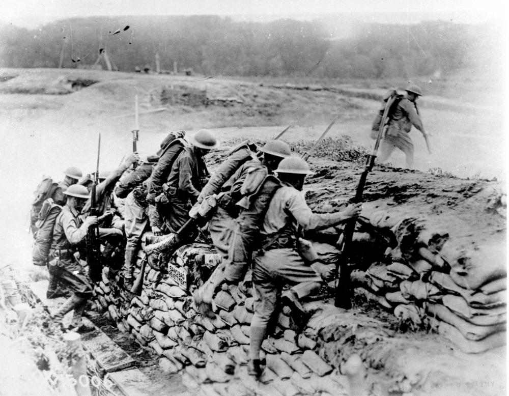American troops carrying guns climb over a sandbag revetment in France during World War I in 1918. (AP Photo)