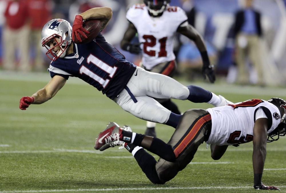 Tampa Bay Buccaneers safety Keith Tandy, right, upends New England Patriots wide receiver Julian Edelman after a catch in the second quarter.(AP)