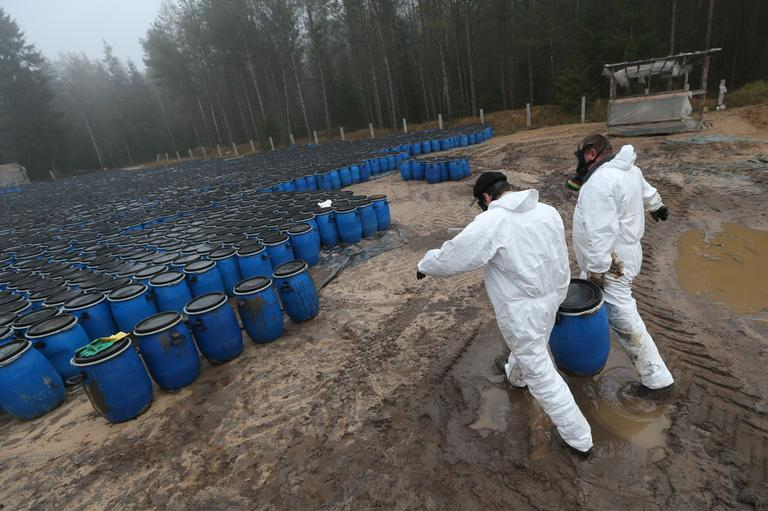 Belarusian Emergency Ministry employees carry plastic barrel with pesticide at a burial site in a forest near the village of Novaya Strazha, some 200 kms (125 miles) southwest of Minsk, Wednesday, Nov. 14, 2012. (AP)