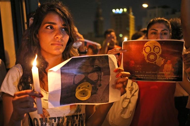 Syrian women who live in Beirut, hold candles and placards during a vigil against the alleged chemical weapons attack on the suburbs of Damascus, in front the United Nations headquarters in Beirut, Lebanon, Wednesday, Aug. 21, 2013. (AP)
