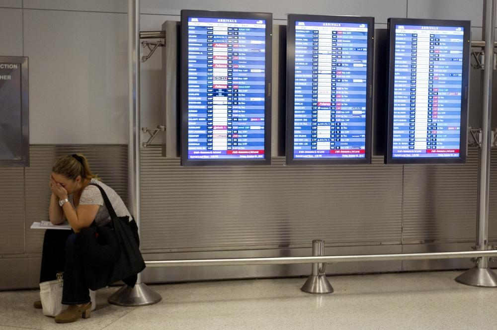 An unidentified American Airlines passenger is trying to make new flight arrangements after her flight was delayed. (AP/J Pat Carter)