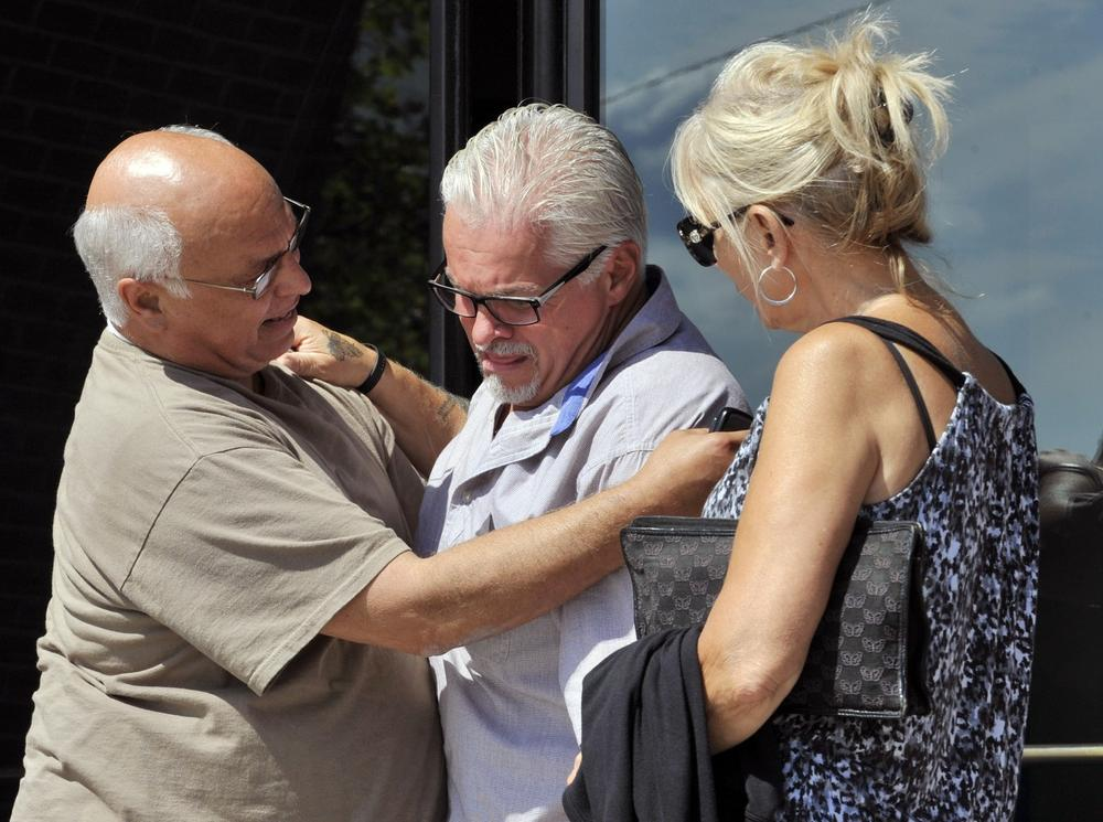 """Steven Davis, brother of Debra Davis, center, is comforted after speaking outside federal court where a jury found James """"Whitey"""" Bulger guilty on several counts of murder, racketeering and conspiracy on Monday. Jurors could not agree whether Bulger was involved in Debra Davis' killing. (Josh Reynolds/AP)"""