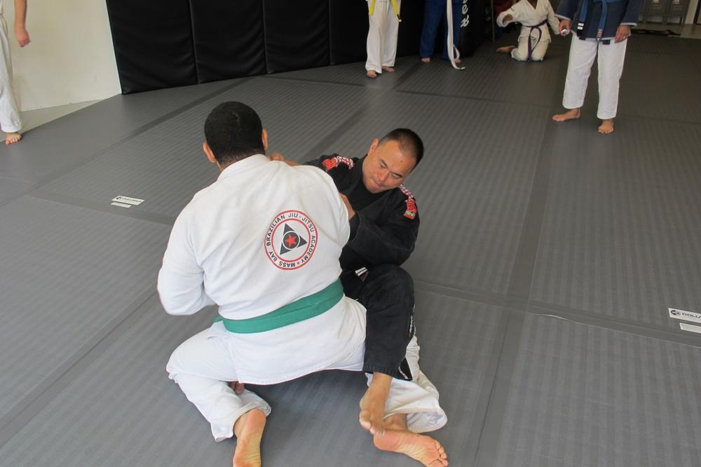 David Shim (in black), a ninth-degree black belt in karate, practices jiu jitsu with a student at his Boston studio. After decades of studying and teaching karate, Shim took up jiu jitsu in 2006. (Doug Tribou/Only A Game)