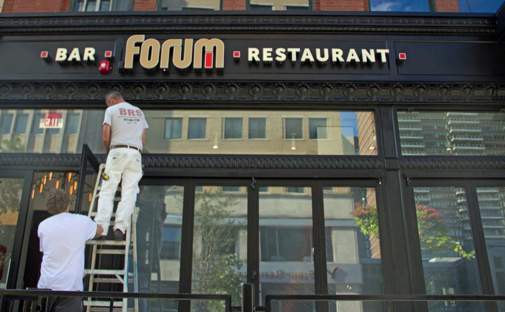 Workers paint the new sign of Forum Bar & Restaurant, the site of the second blast during the Boston Marathon on April 15. (Meghna Chakrabarti/WBUR)