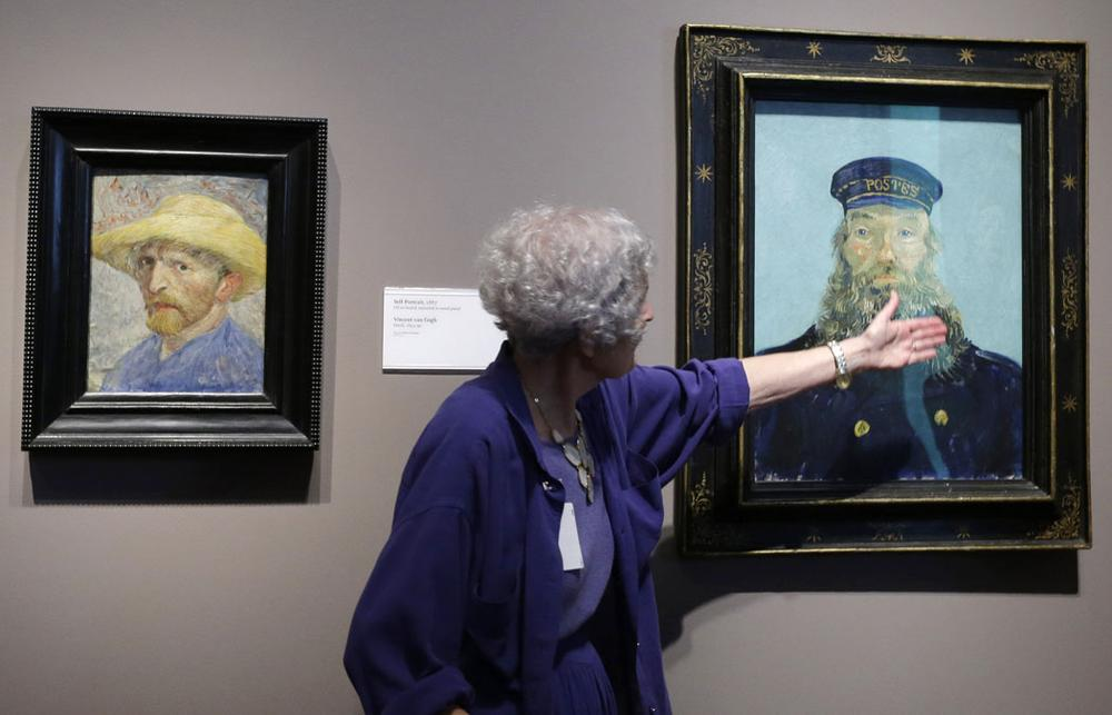 "Detroit Institute of Arts docent Lea Schelke points out details in the ""Portrait of Postman Roulin"" by Van Gogh displayed at the museum in Detroit. (AP Photo/Carlos Osorio)"