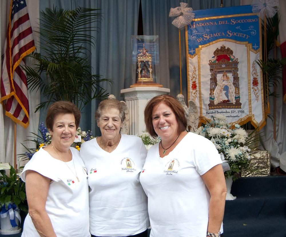 Anna Campo with her daughters Rita Sacco (left) and Nadine Solimine in front of the altar at the Madonna Del Soccorso di Sciacca Society. (Greg Cook/WBUR)