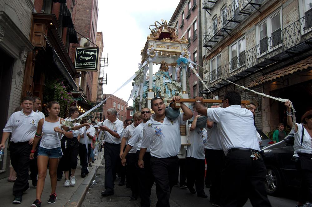 """""""The Grand Procession"""" takes all Sunday afternoon and evening to snake through the streets of Boston's North End accompanied by marching bands. (Greg Cook/WBUR)"""