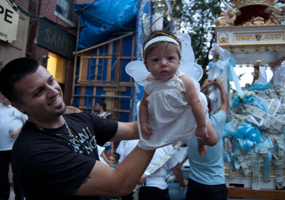 Three-month-old Antonia Graziano, dressed as an angel, is held up by her father Dave. (Greg Cook/WBUR)