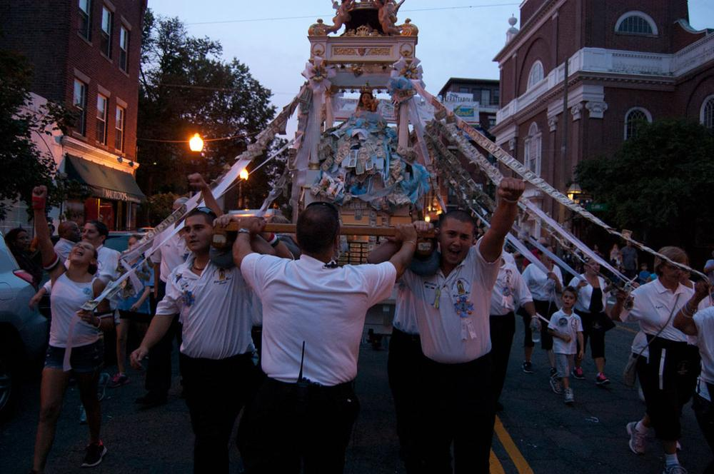 Statue carriers cheer along with the marching band music. (Greg Cook/WBUR)